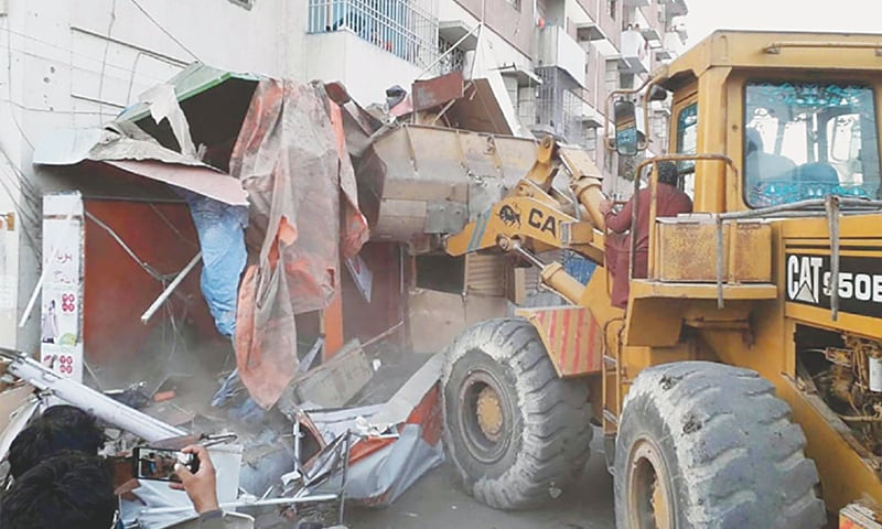 A DEMOLITION squad removes encroachments at KDA Market in Gulshan-i-Iqbal on Friday.—PPI