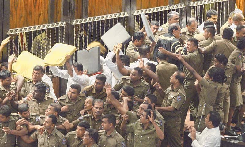 Colombo: Police escort Sri Lanka's parliament speaker Karu Jayasuriya (top-right, in black and gold) as aides hold up cushions to protect him and themselves from projectiles thrown by rival legislators in the assembly hall on Friday. Sri Lanka's political crisis escalated with the sacked prime minister demanding his job back shortly after passing another no-confidence motion against his controversial successor amid unprecedented rioting in parliament.—AFP            Report on Page 14
