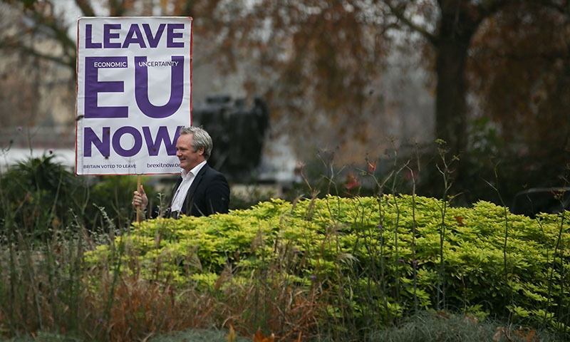 A pro-Brexit supporter stands with a placard demanding to leave the European Union immediately near the Houses of Parliament in London on November 16, 2018. — AFP