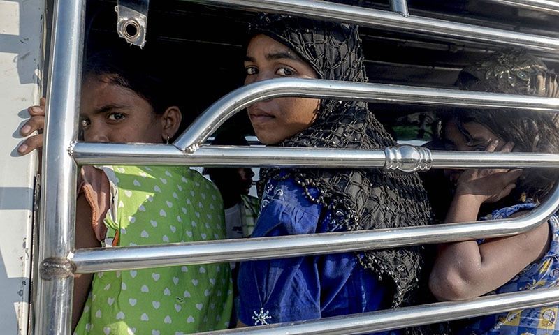 Rohingya Muslim women ride a police vehicle in Kyauktan township south of Yangon on November 16, 2018 after their boat washed ashore. — AFP