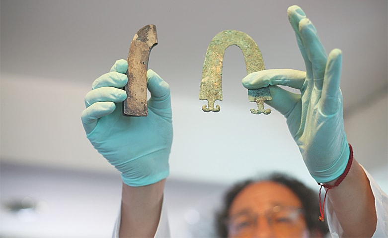 AN ARCHAEOLOGIST shows jewellery from one of the tombs found at a Bolivian quarry near the capital of La Paz.—AP