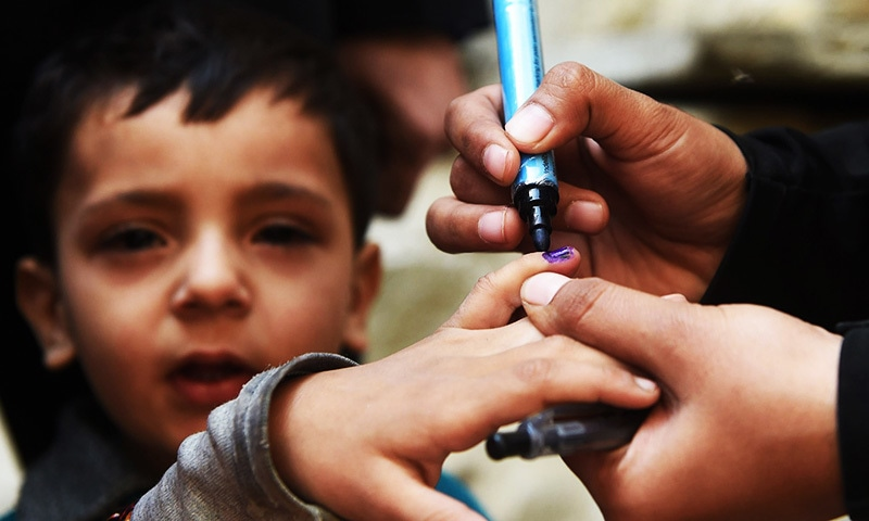 In this photograph, a Pakistani health worker marks a child's finger after administering polio drops outside her house during a door-to-door polio immunization campaign.—AFP/File