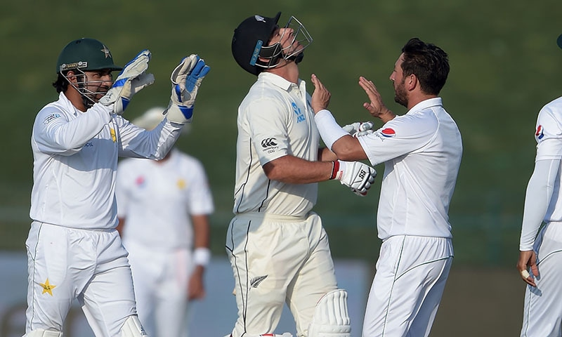 Pakistani captain and wicketkeeper Sarfraz Ahmed (L) celebrates with teammate Yasir Shah (R) after dismissed New Zealand batsman Colin de Grandhomme (C) during the third day of the first Test cricket match between Pakistan and New Zealand at the Sheikh Zayed International Cricket Stadium in Abu Dhabi on November 18, 2018. —AFP