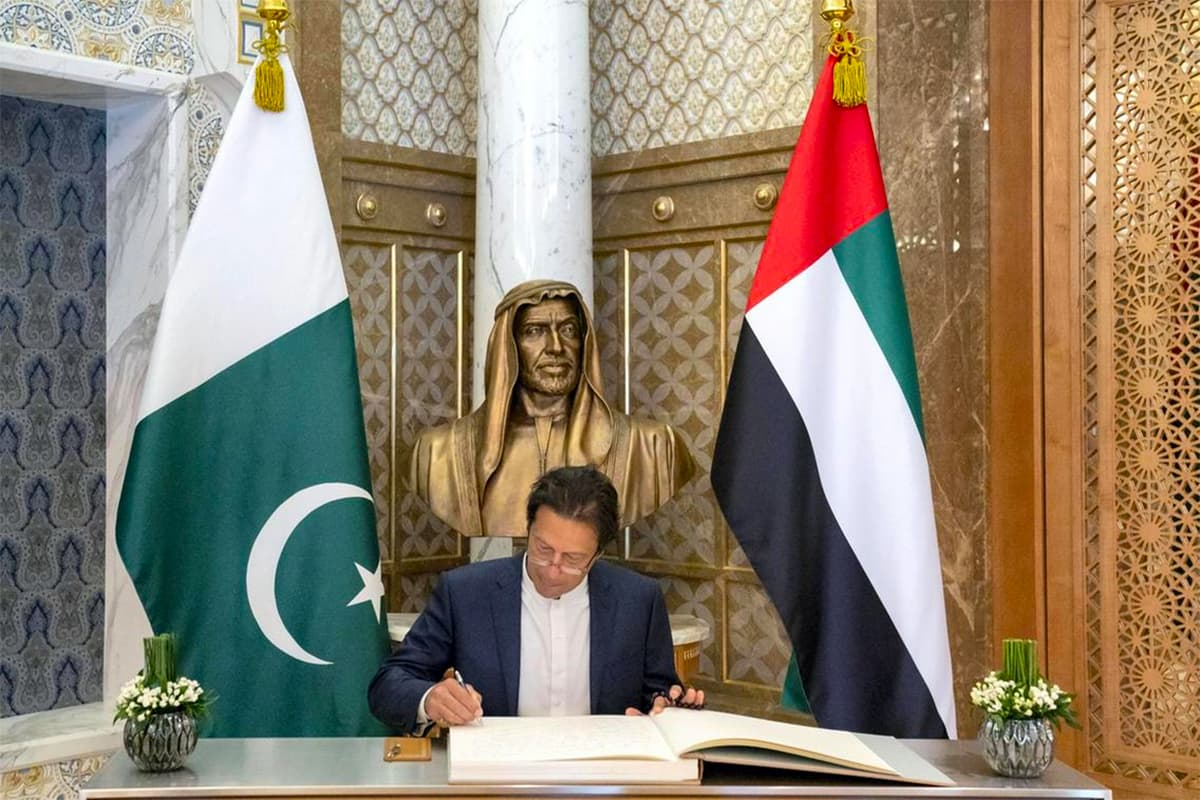Prime Minister Khan signs a guest book in Abu Dhabi. — Photo courtesy UAE Ministry of Presidential Affairs