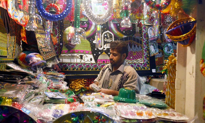 Man sells souvenirs at a stall at Ghanta Ghar Bazar, Peshawar, ahead of Eid-i-Miladun Nabi. — APP