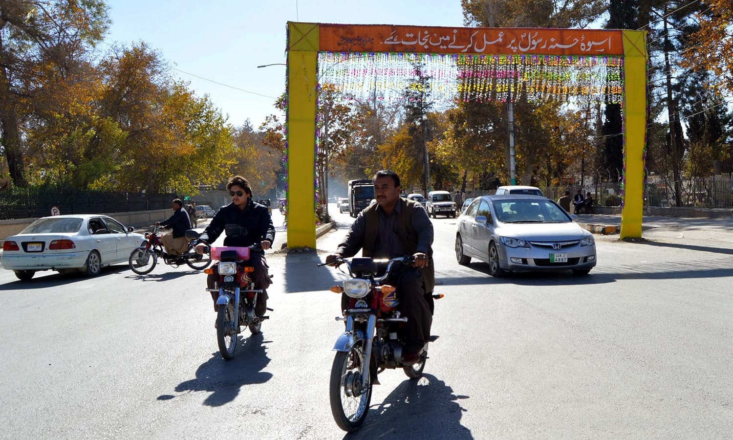 Motorcyclists pass by decorations being put up on TNT Chowk in Quetta ahead of Eid Miladun Nabi. — APP