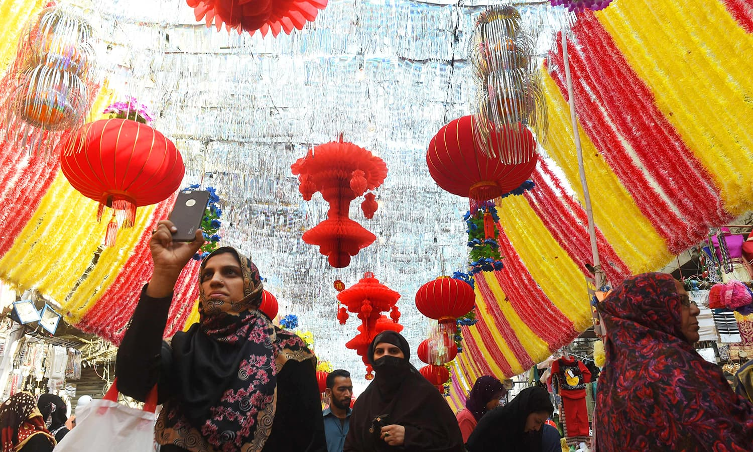 A Pakistani woman takes pictures of a decorated market in Lahore ahead of Eid Miladun Nabi. — AFP