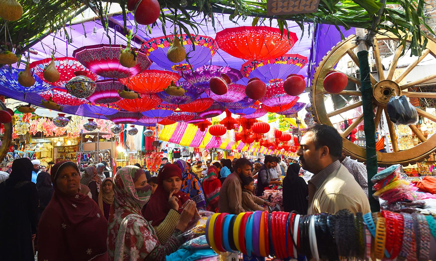 Pakistani shoppers throng a decorated market in Lahore ahead of Eid-i-Miladun Nabi. — AFP