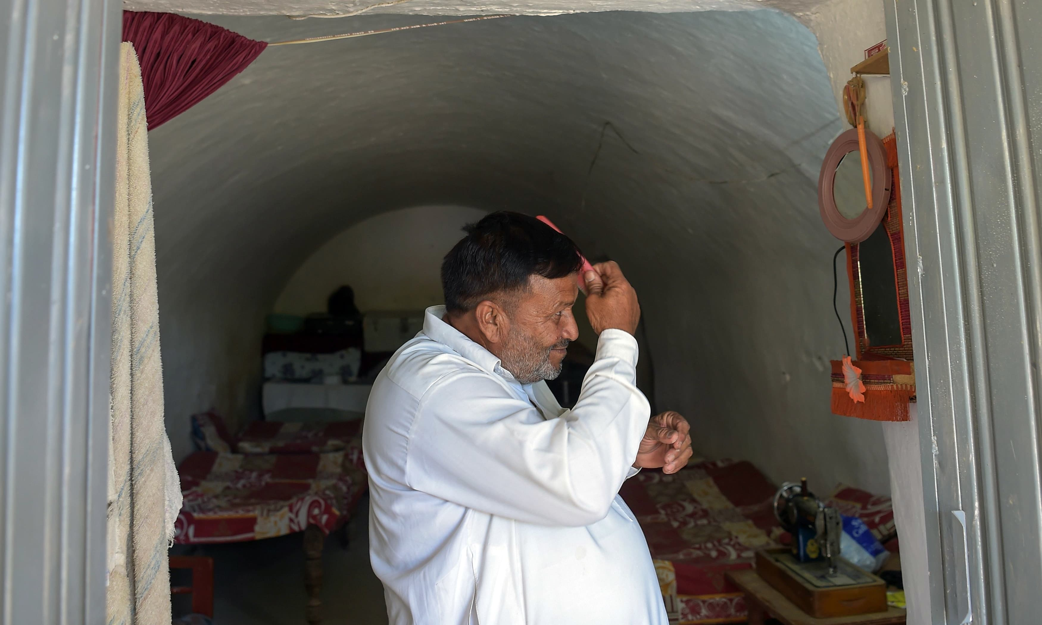 Haji Abdul Rasheed combs his hair at the entrance to his cave room in Nikko village near Hasan Abdal. —AFP