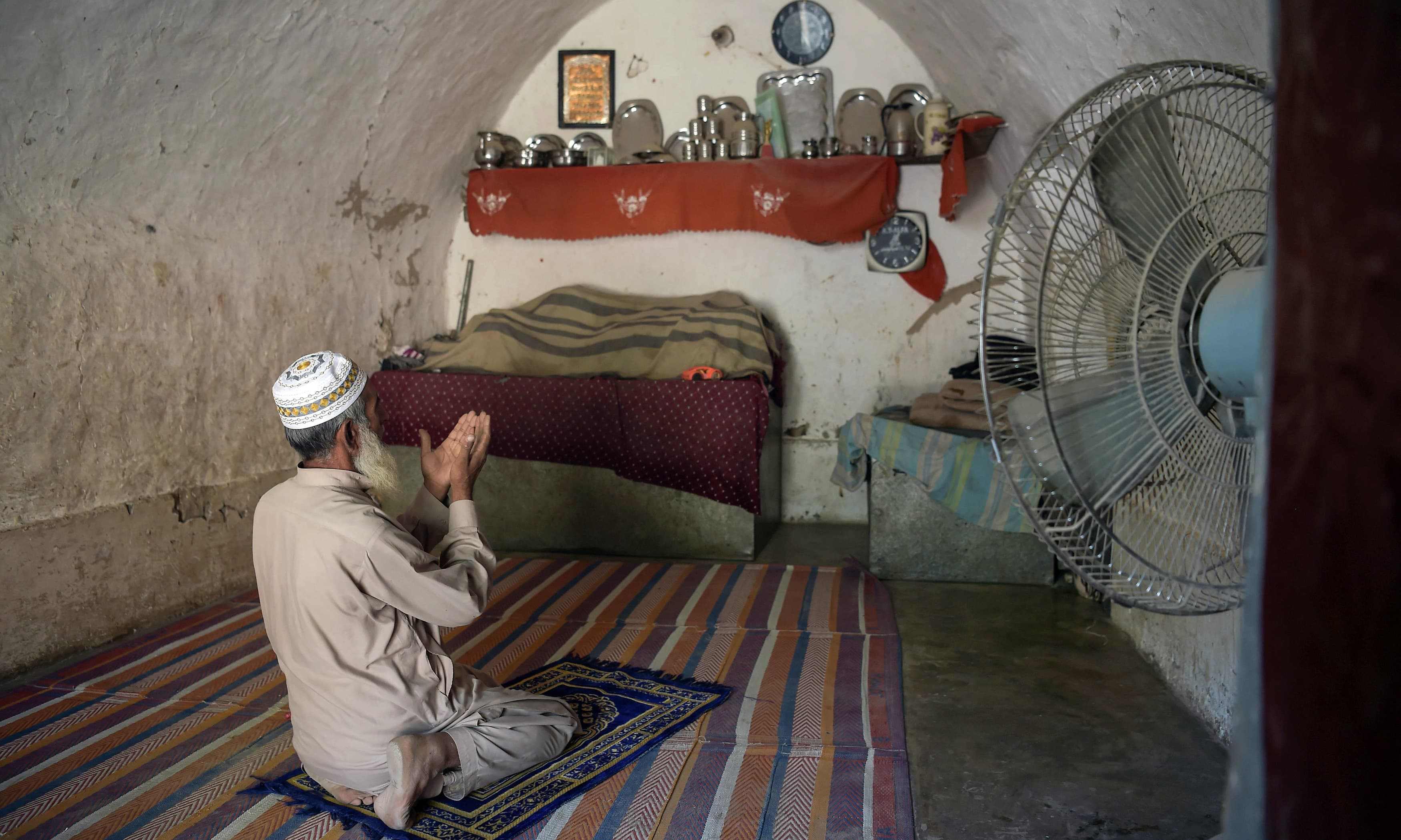 Faqeer Gul offers noon prayers in his cave room in Nikko village. —AFP