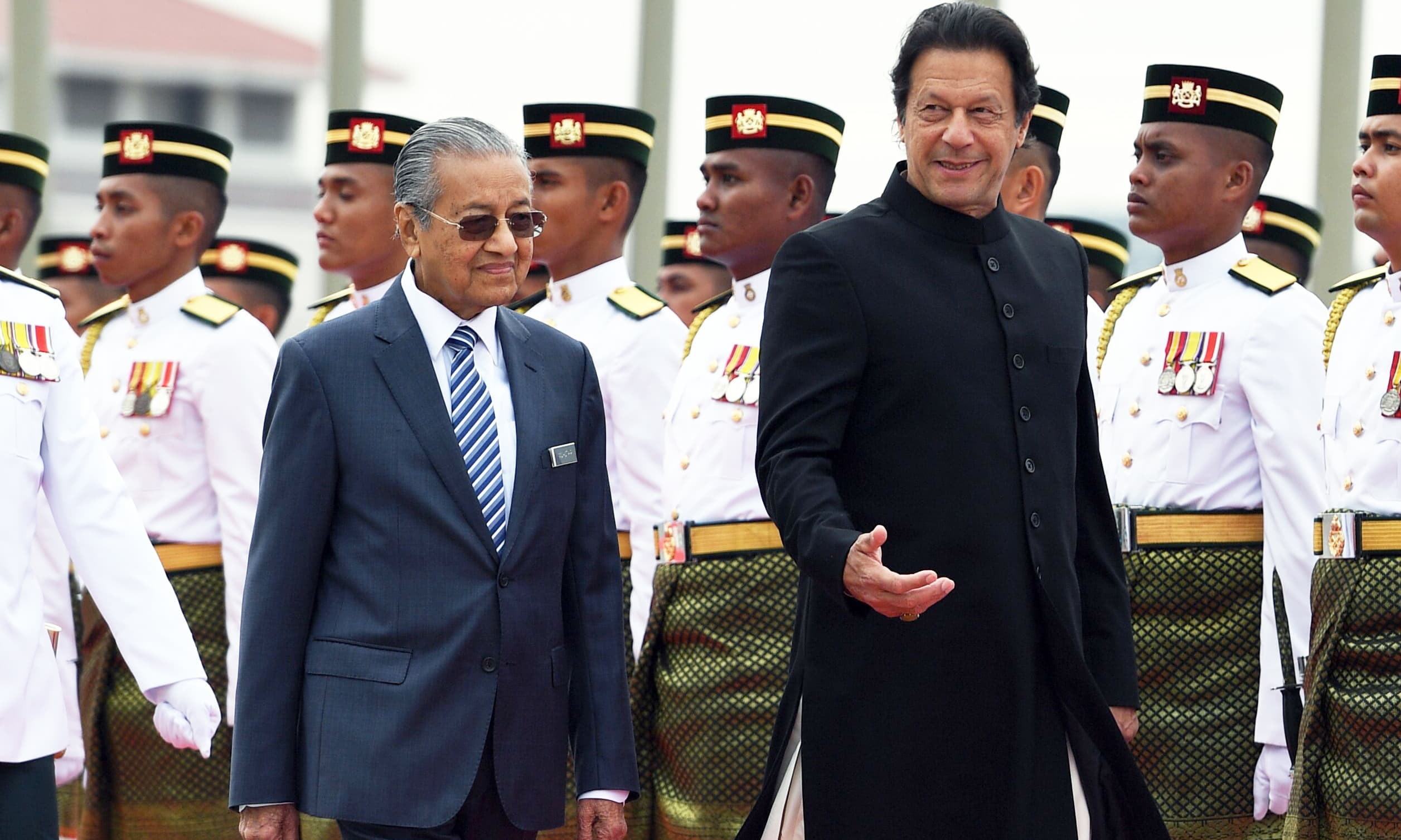 PM Imran Khan speaks to his Malaysian counterpart Mahathir Mohamad during a welcoming ceremony in Putrajaya. —AFP