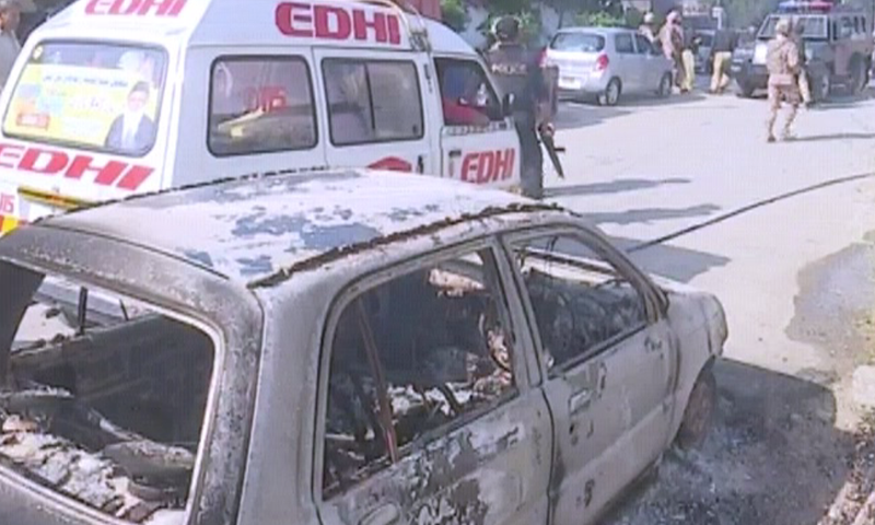 A photograph showing a burnt out car next to an Edhi ambulance at the site of the attack. ─ DawnNewsTV