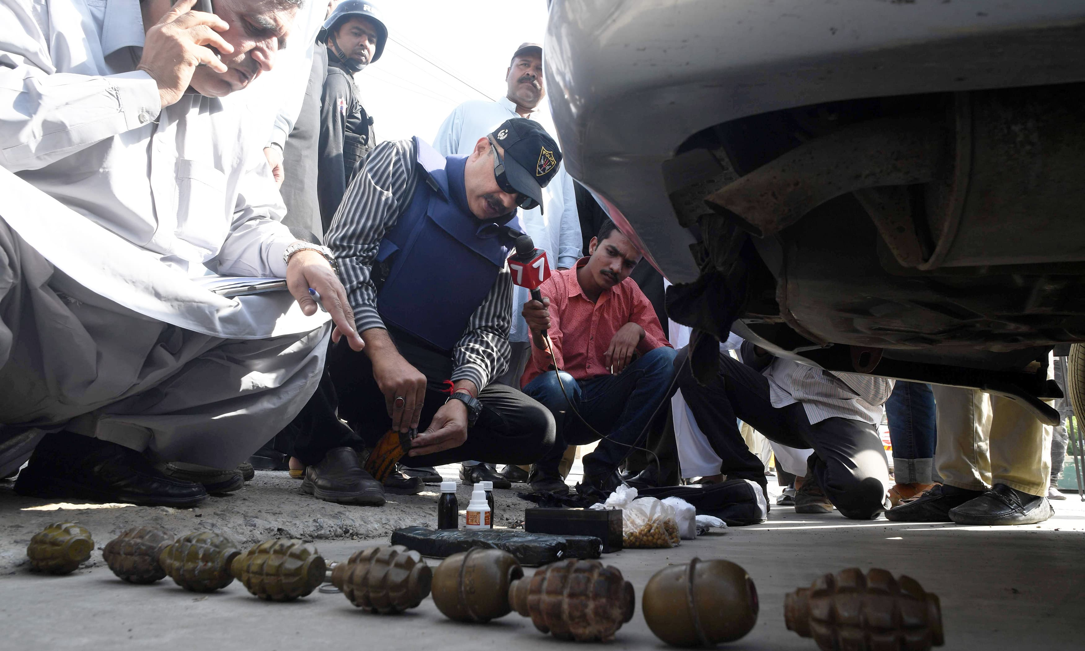 Investigators look at the belongings of attackers including grenades outside the Chinese consulate after an attack in Karachi. —AFP