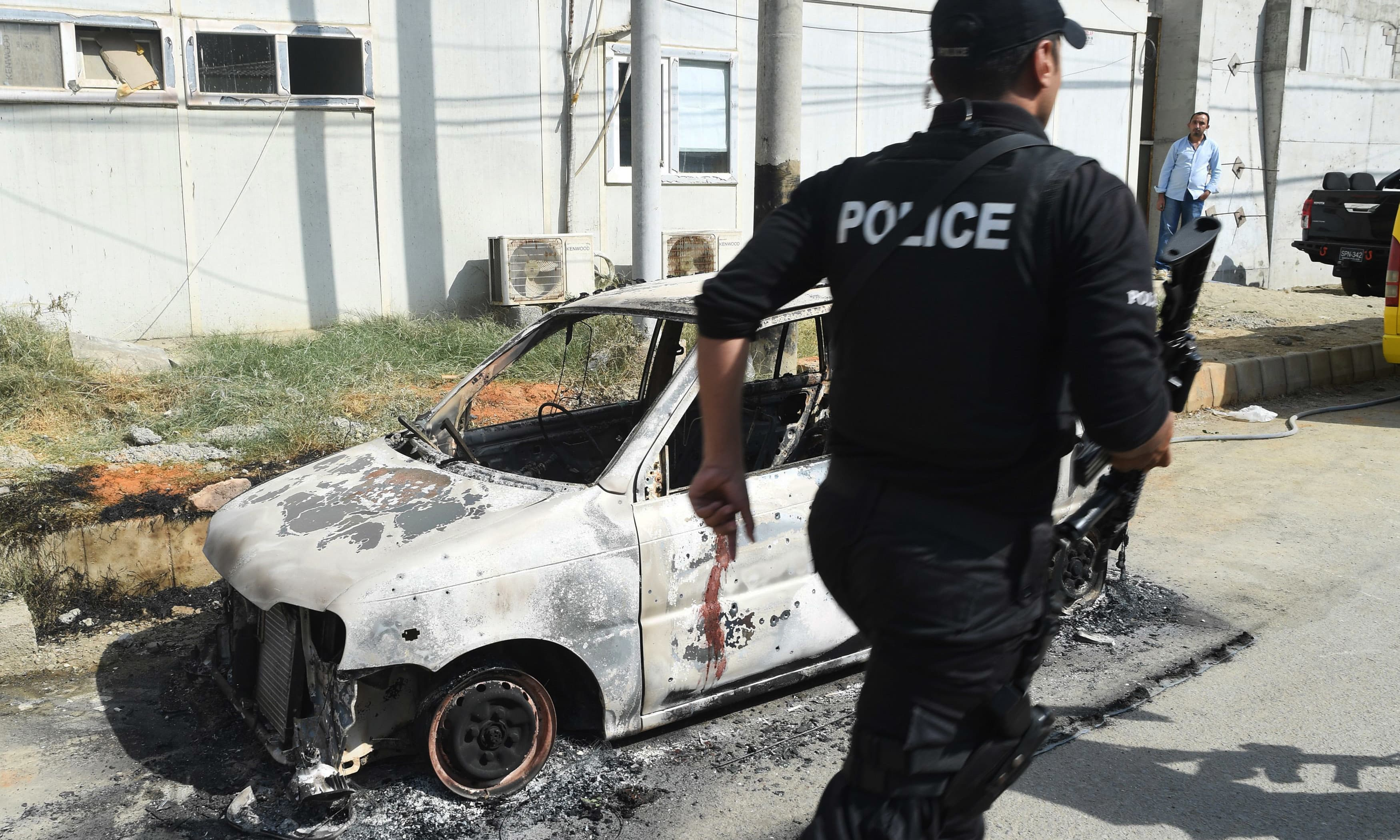 A police commando walks past a burnt vehicle outside the Chinese consulate. —AFP