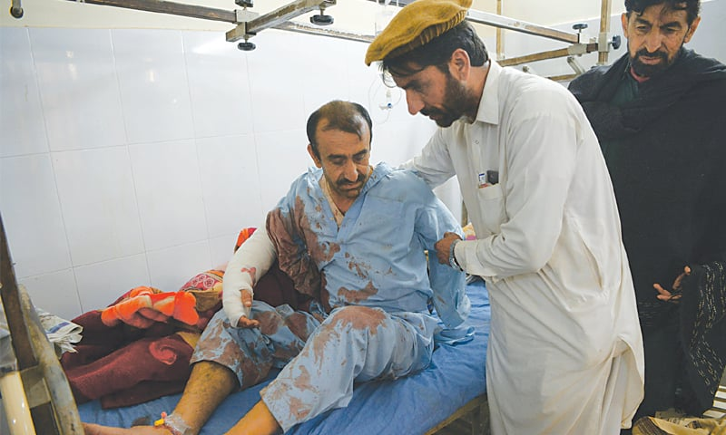Kohat: Relatives of a victim assist him during the treatment at a hospital on Friday.—Abdul Majeed Goraya/White Star