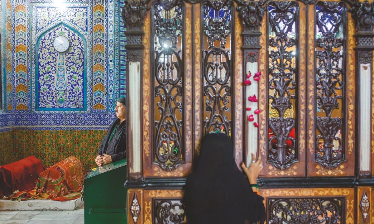 A woman peeking at the grave of Shah Abdul Latif Bhitai
