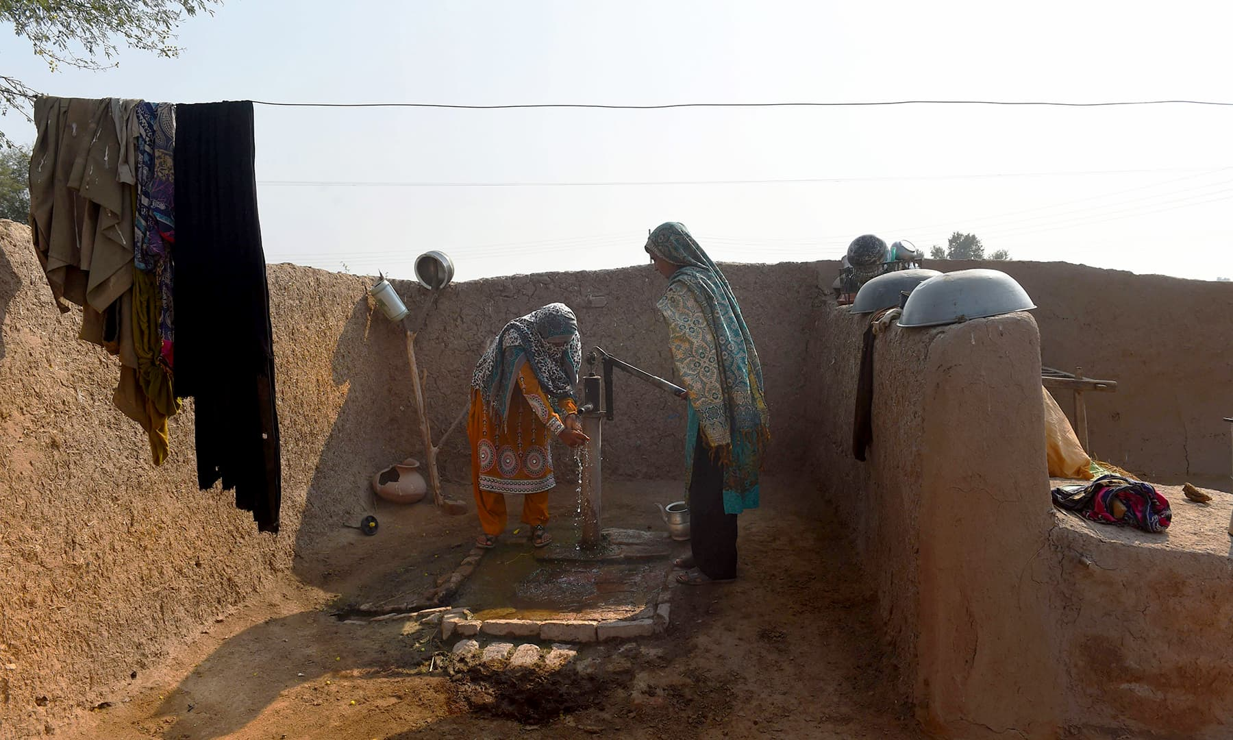 A woman washes her hands at a hand pump next to the toilet. —AFP