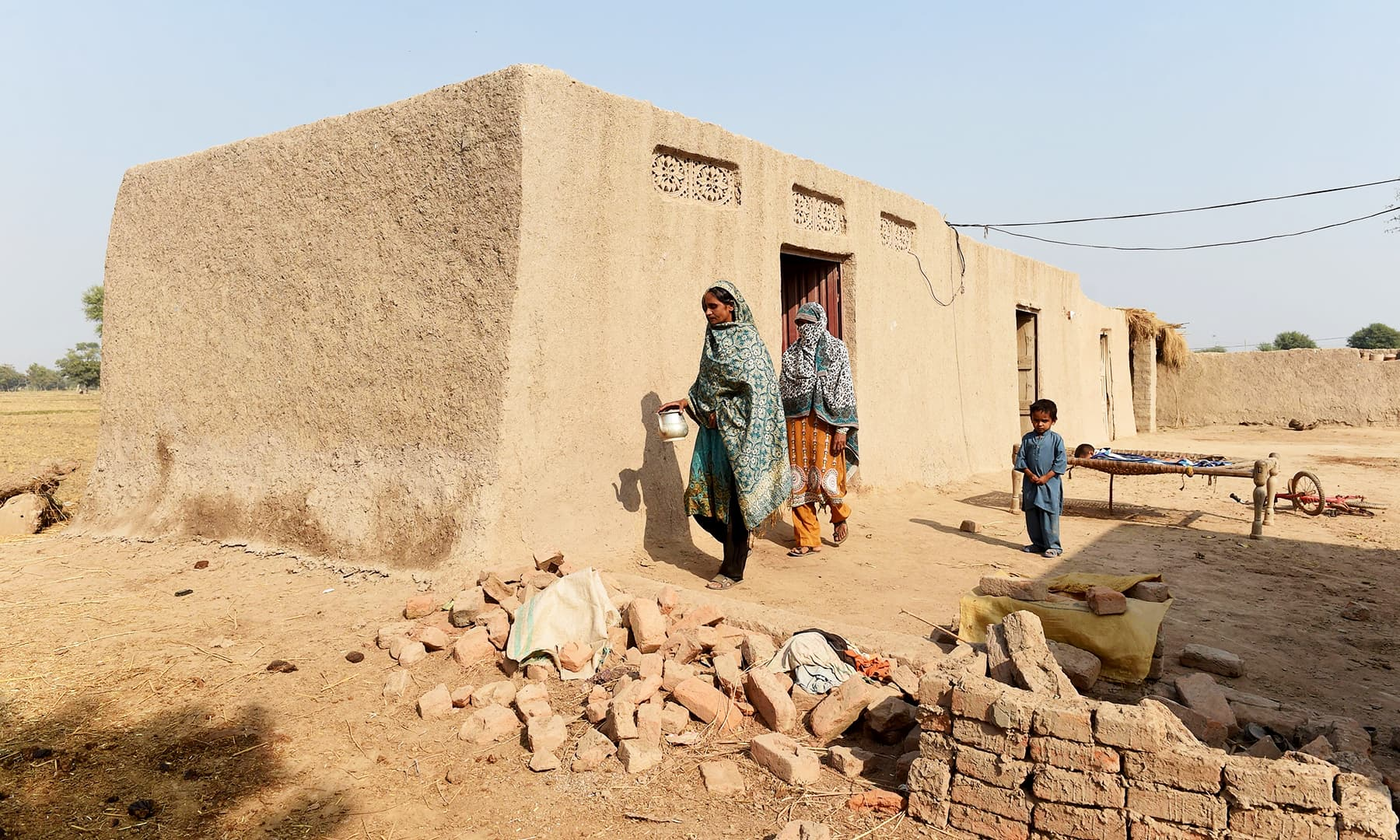 Women walk towards a toilet in Basti Ameerwala village in central Punjab. —AFP