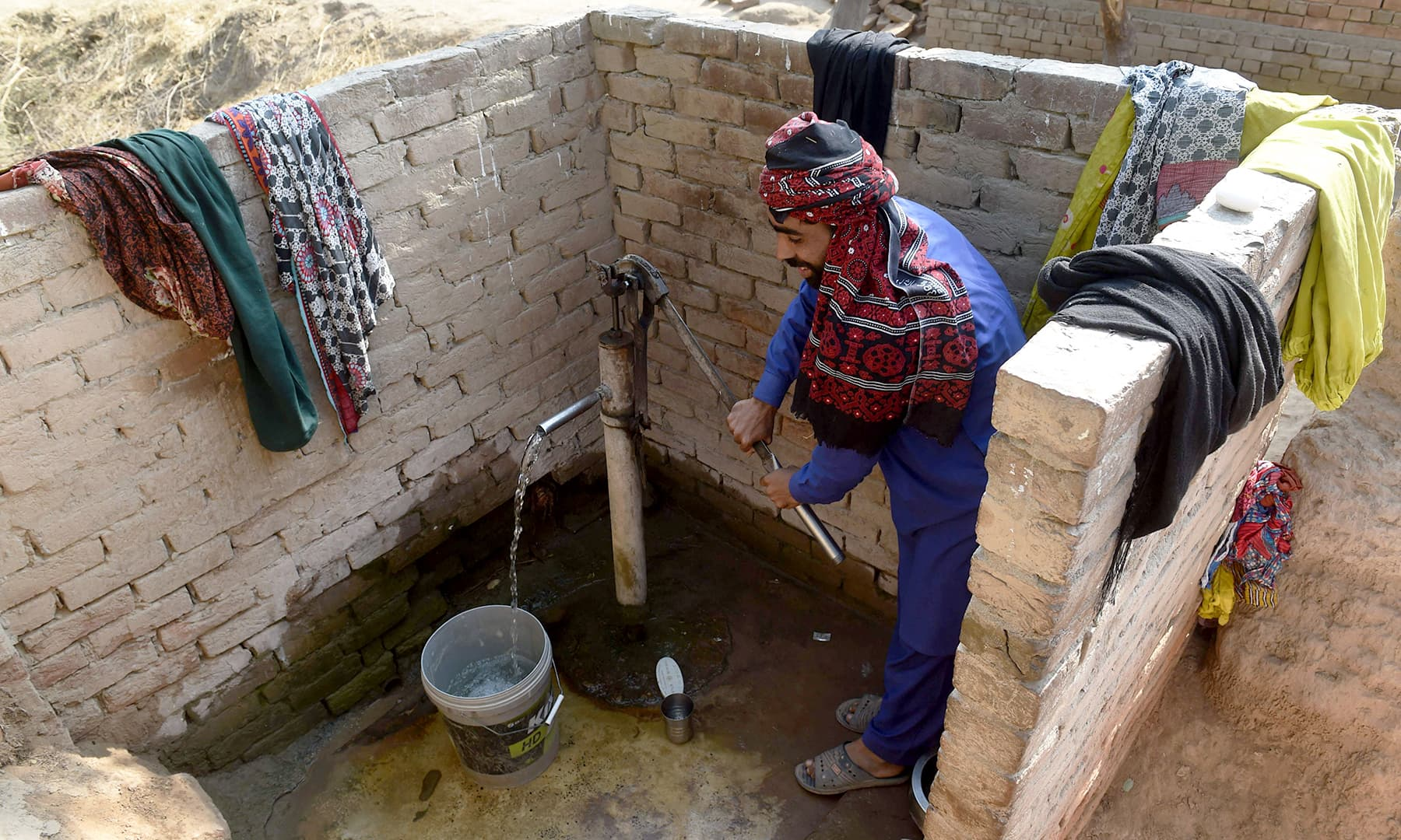 A man pumping water to wash up, next to a toilet built by non-profit Lodhran Pilot Project (LPP). —AFP