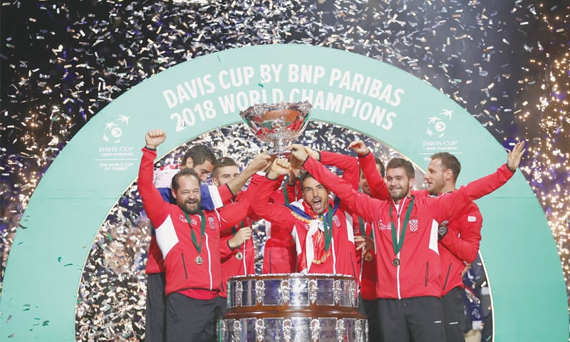 LILLE: Croatian players lift the trophy after winning the Davis Cup final against France on Sunday.—AP