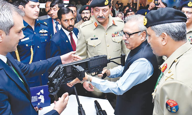 KARACHI: President Arif Alvi looks at a weapon that can take shots around corners during his visit to the 10th International Defence Exhibition and Seminar at the Expo Centre on Tuesday—AFP