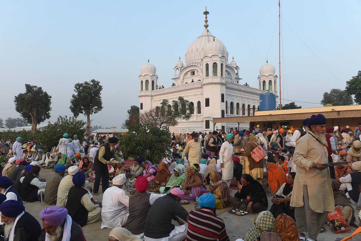 Sikh pilgrims wait for food at the shrine of their spiritual leader Guru Nanak Dev in Kartarpur. — AP