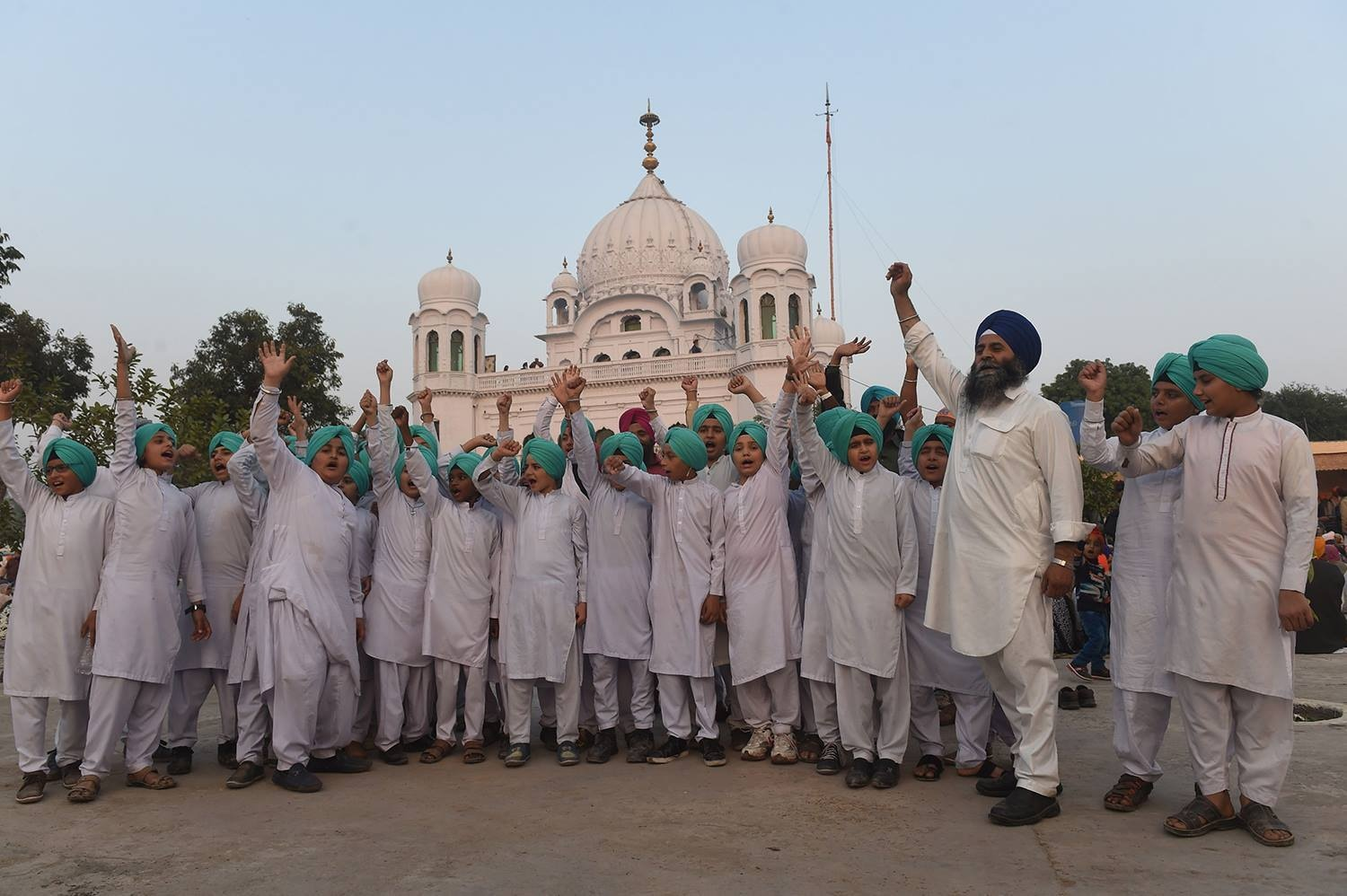 Sikh children shout slogans in front of the Kartarpur Gurdwara Sahib after a groundbreaking ceremony for the Kartarpur Corridor. — AFP