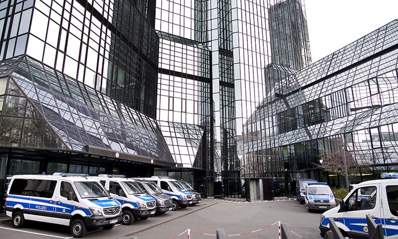 Police cars stand in the backyard of Deutsche Bank headquarters during a raid in Frankfurt, Germany on Thursday. — AP