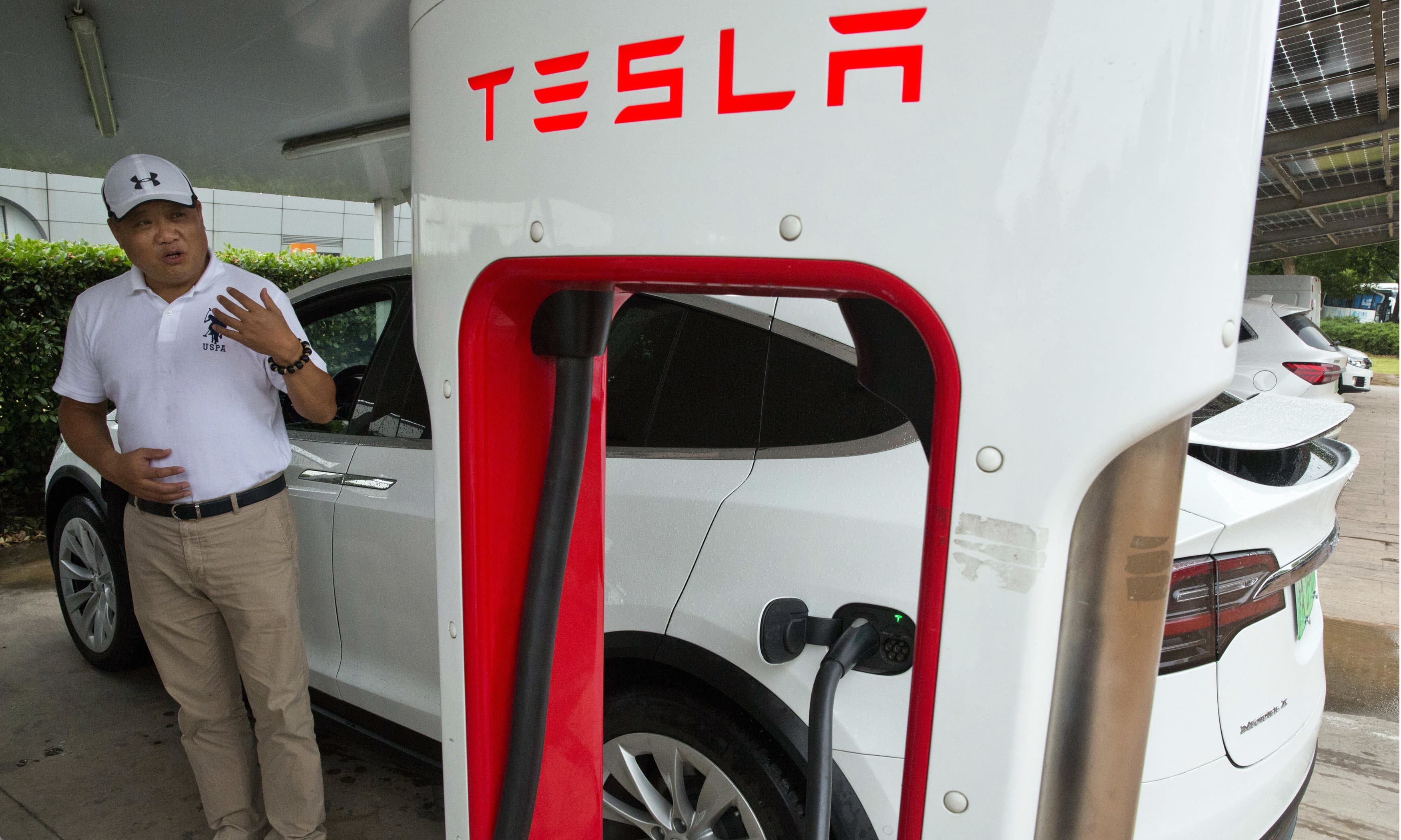 Shan Junhua chats about privacy near his white Tesla while charging it in Shanghai. —AP