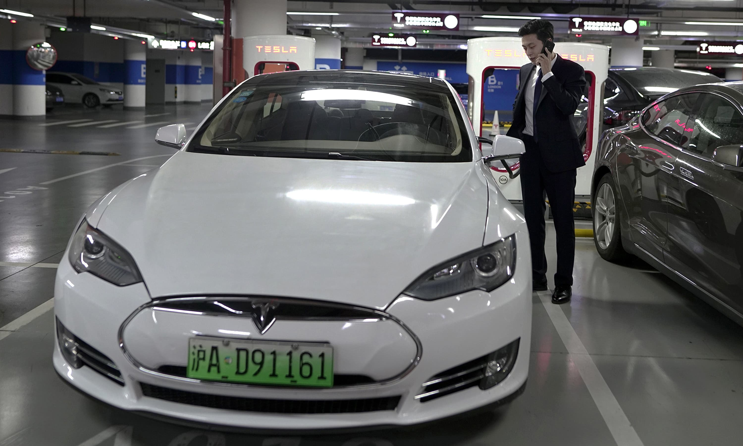 An Baojia makes a call near his Tesla vehicle at a charging station in Shanghai. —AP