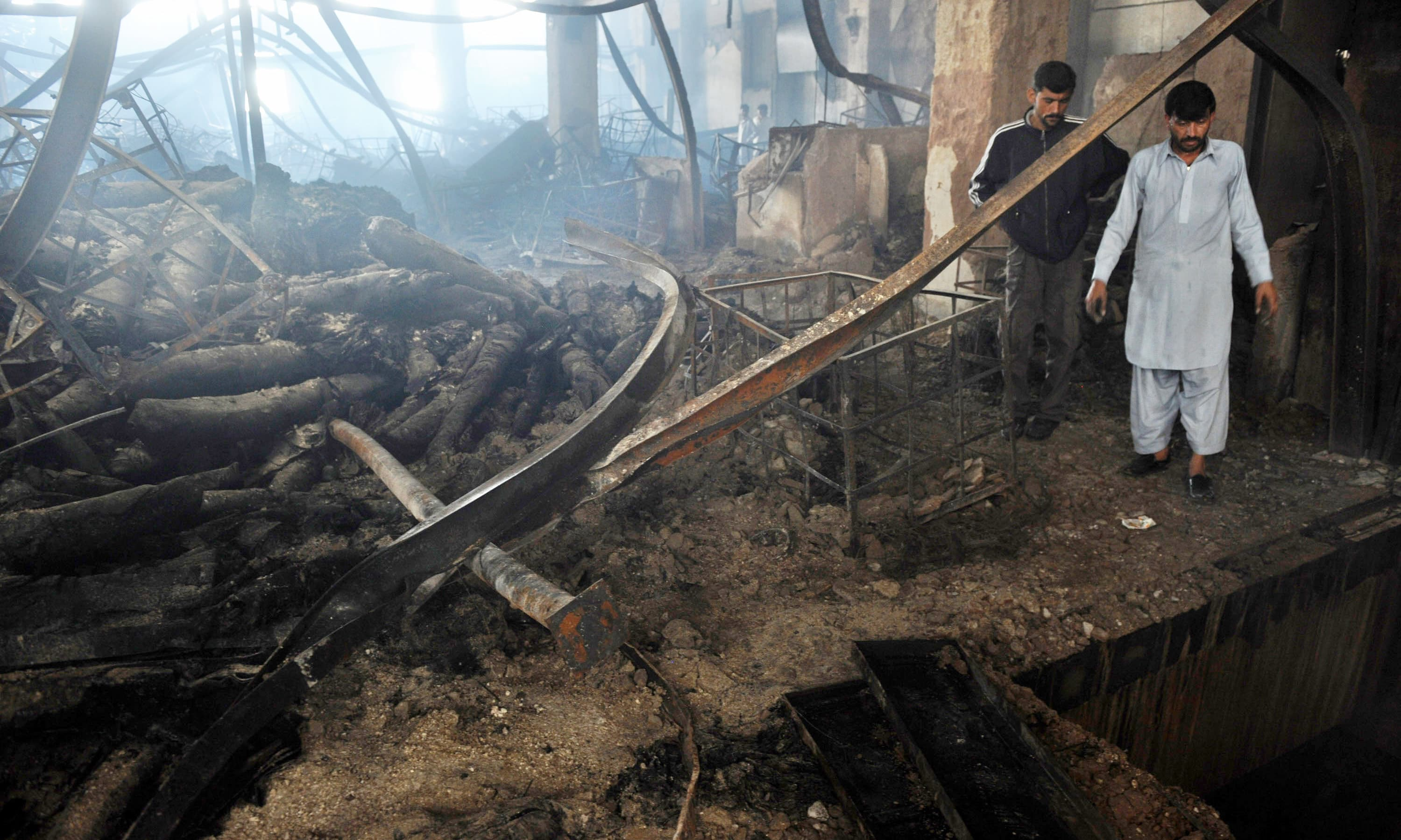 People gather in the factory following the fire in which at least 289 people died. —AFP/File