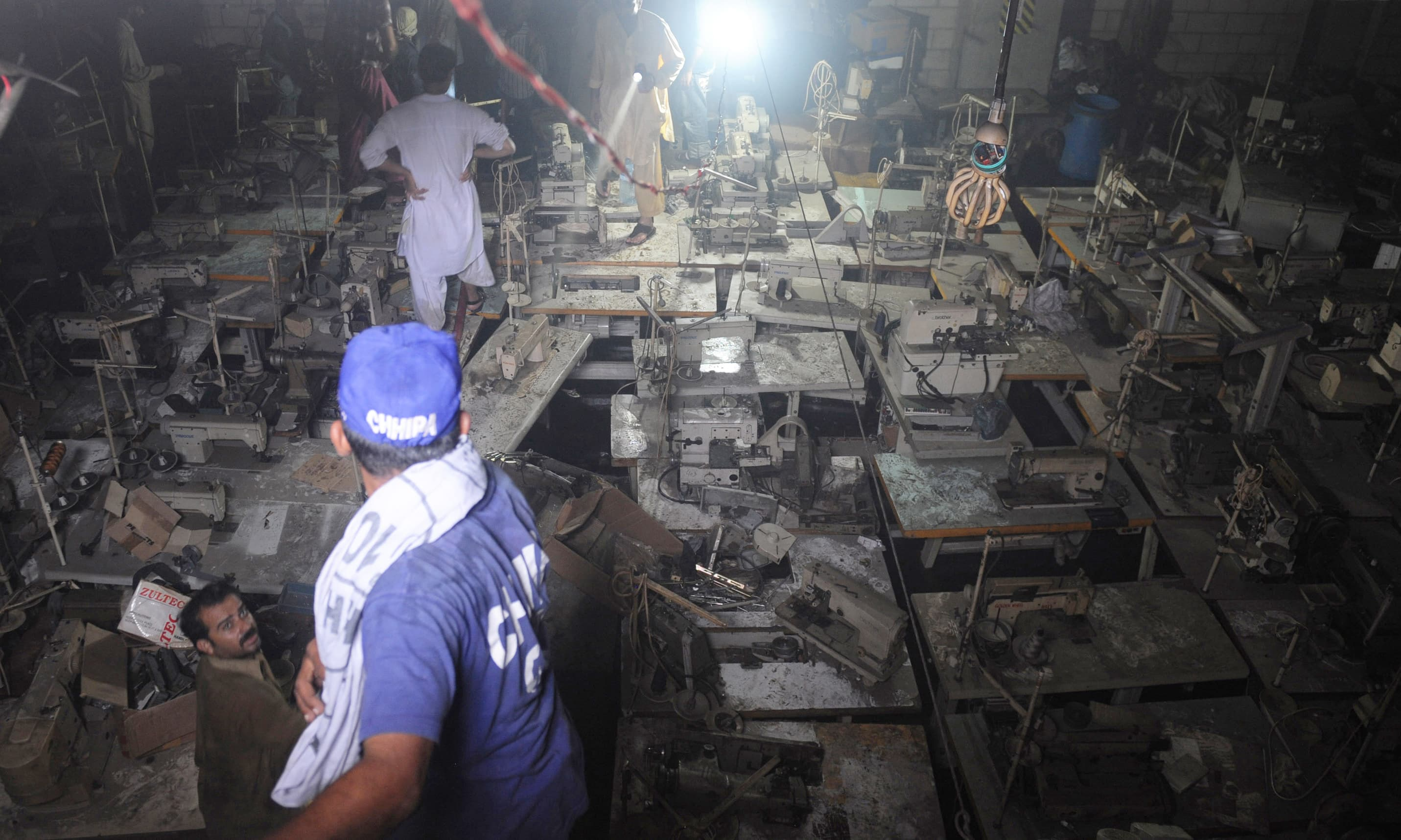 Rescue officials work inside the charred factory. —AFP/File