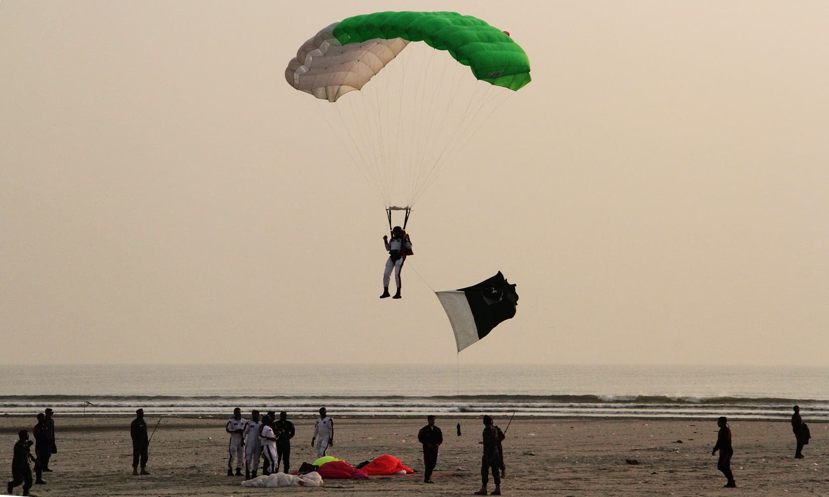 Commander SSG-N Imran Rana carries national flag during para jump at sea view. —ISPR