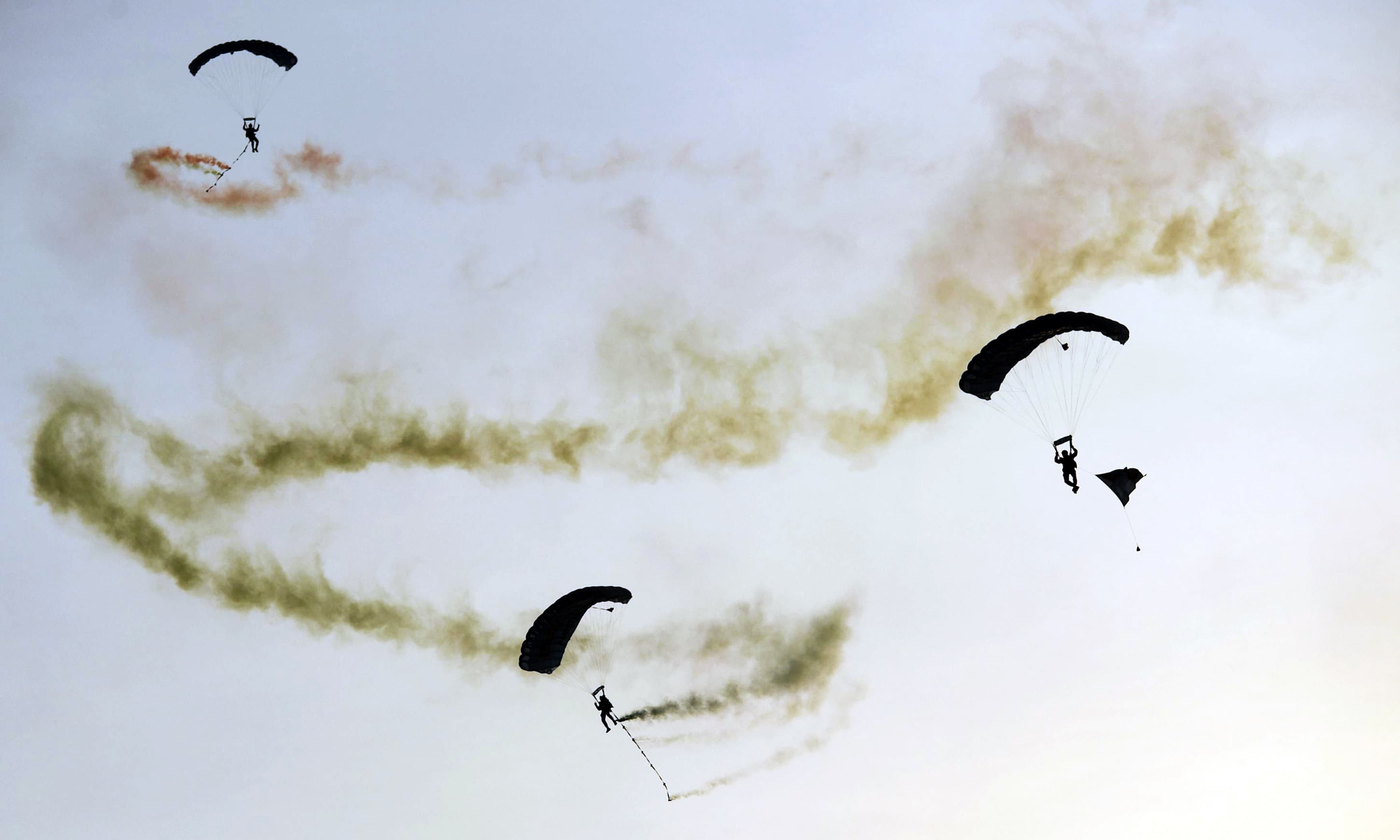 Paratroopers descend on parachutes during the 10th IDEAS expo. —AFP