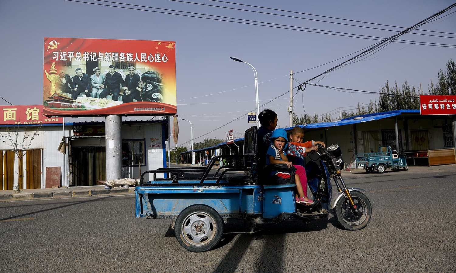In this Sept 20, 2018, file photo, an Uighur woman shuttles school children on an electric scooter as they ride past a propaganda poster showing China's President Xi Jinping joining hands with a group of Uighur elders in Hotan, in western China's Xinjiang. — AP