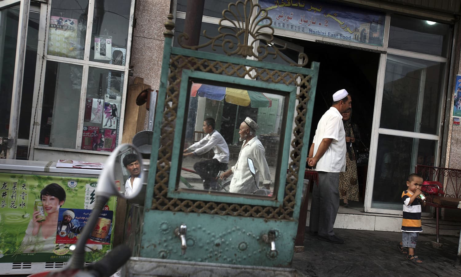 In this Aug 6, 2008, file photo, Uighurs are seen outside a restaurant in Kashgar in China's western Xinjiang province. — AP