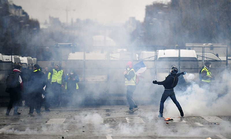 A demonstrator throws projectiles at police on the Champs Elysees avenue in Paris during a protest of Yellow vests (Gilets jaunes) against rising oil prices and living costs. — AFP