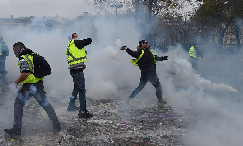 Demonstrators throw back tear gas canisters at police during a protest of Yellow vests (Gilets jaunes) against rising oil prices and living costs. — AFP