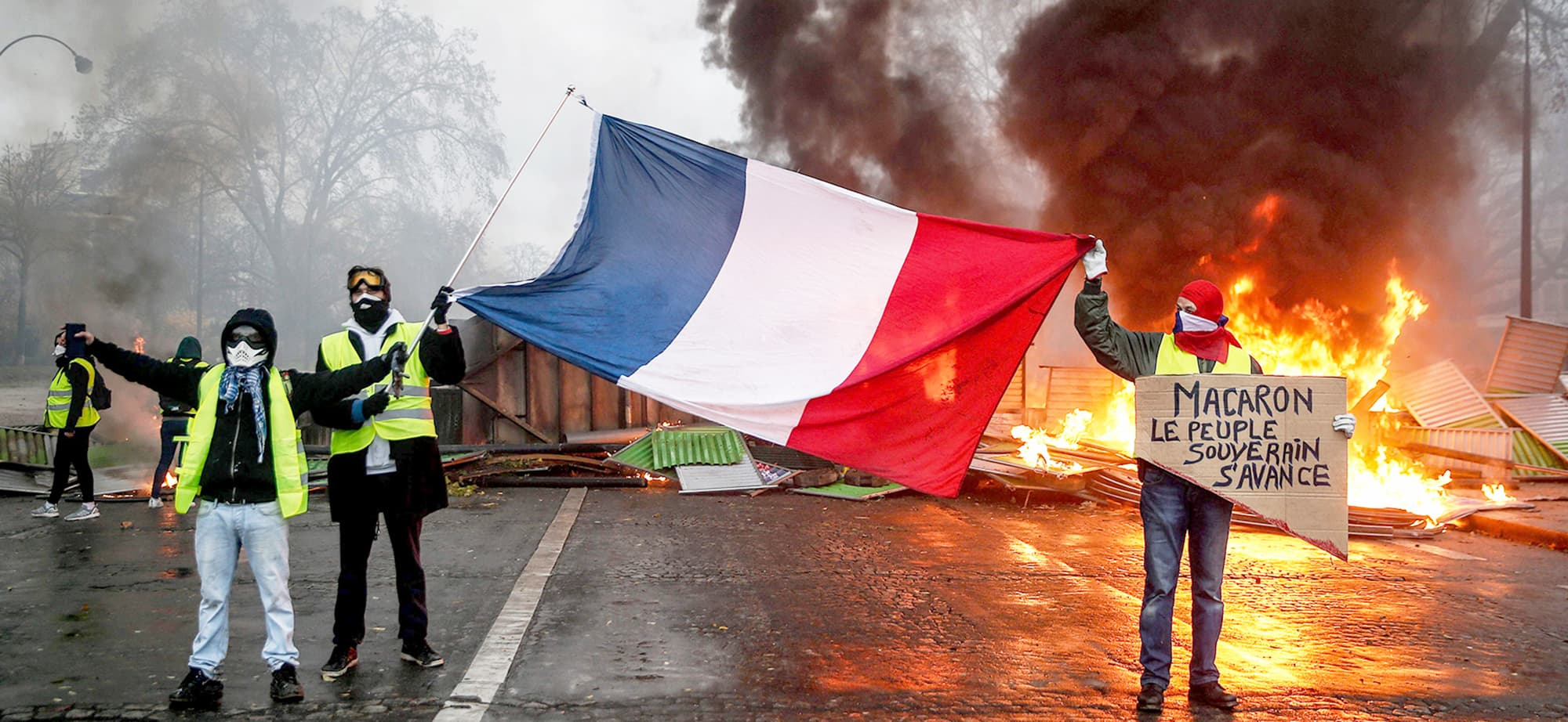TOPSHOT - Protesters hold a French flag near a burning barricade during a protest of Yellow vests (Gilets jaunes) against rising oil prices and living costs, on December 1, 2018 in Paris. (Photo by Abdulmonam EASSA / AFP) — AFP or licensors