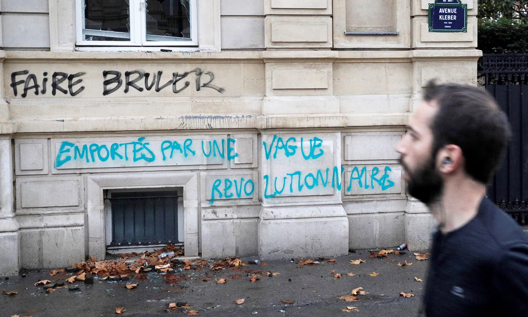 """A man looks at an inscription reading """"Burn"""" and another """"Washed away by a revolutionary wave"""". —AFP"""