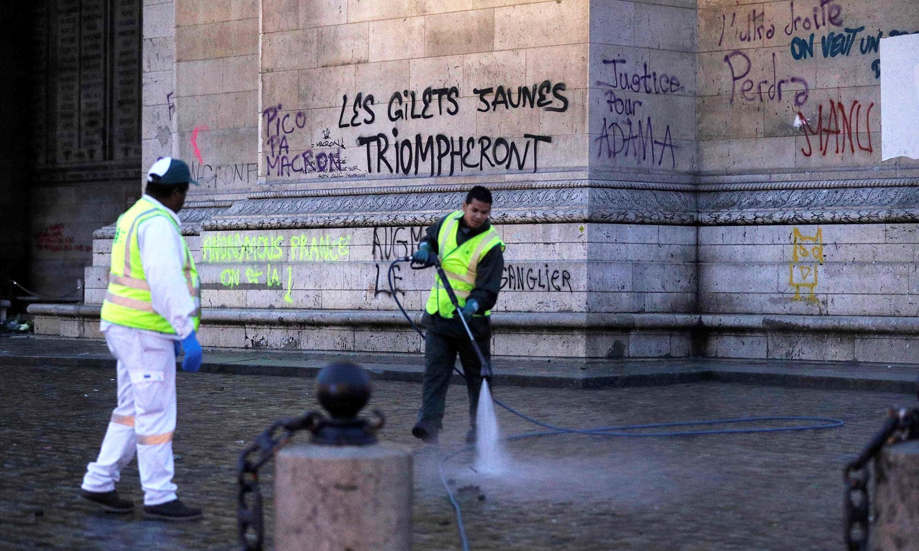 Municipal employees clean the ground in front of the Arc of Triomphe covered with inscriptions.—AFP