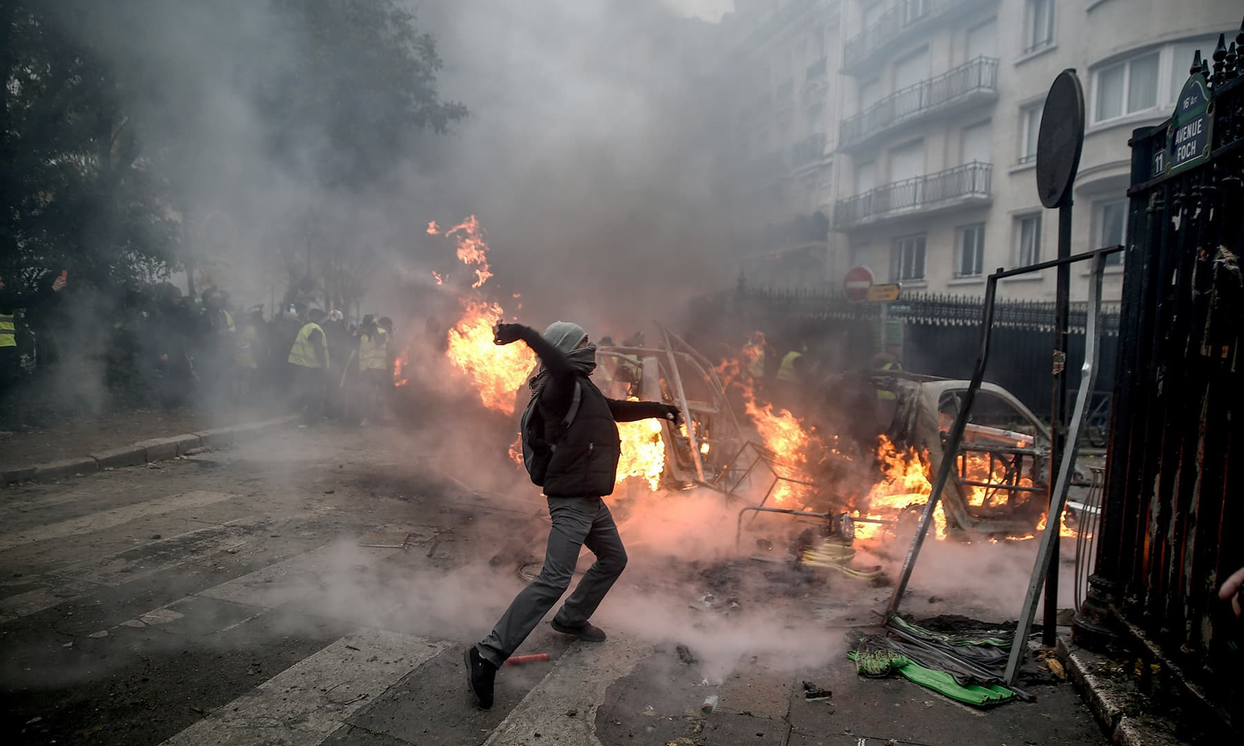 A protester throws projectile at riot police. —AFP