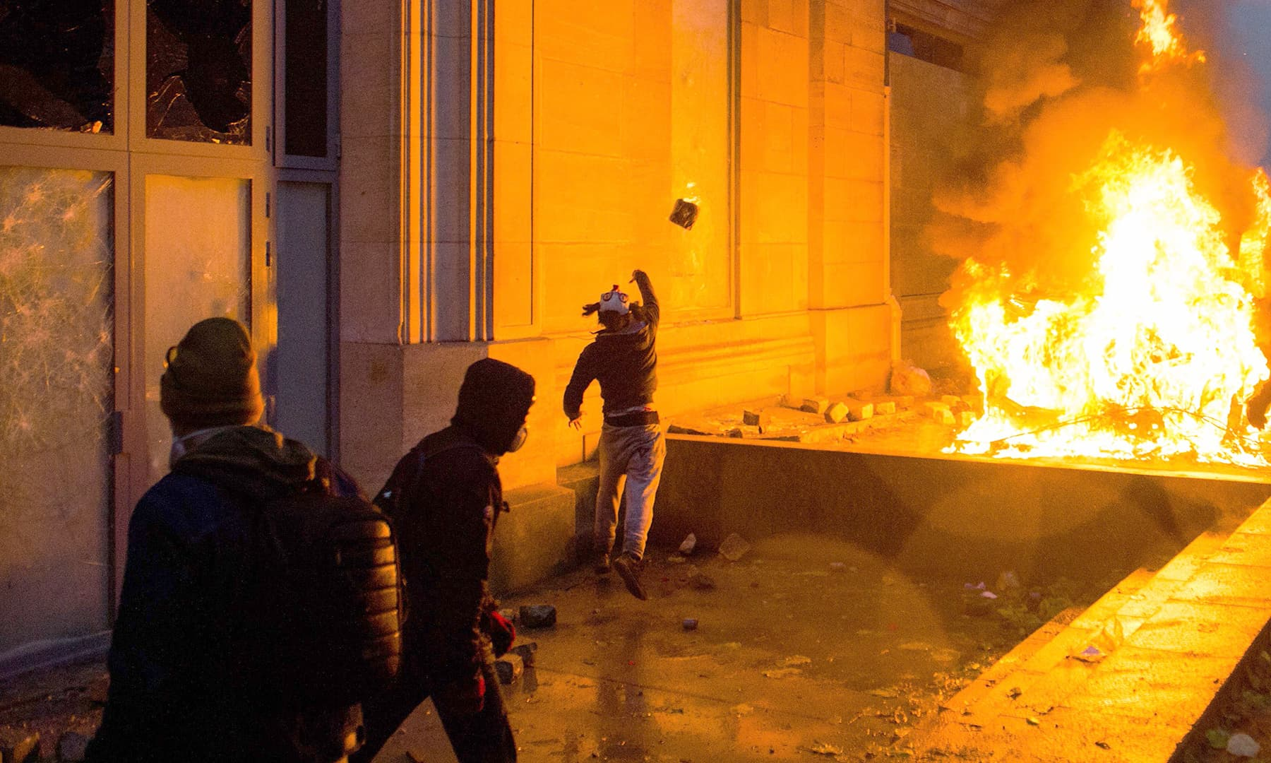 A man throws a stone next to the broken windows of the Musee de l'Orangerie and a burning vehicle on the Tuileries Garden. —AFP