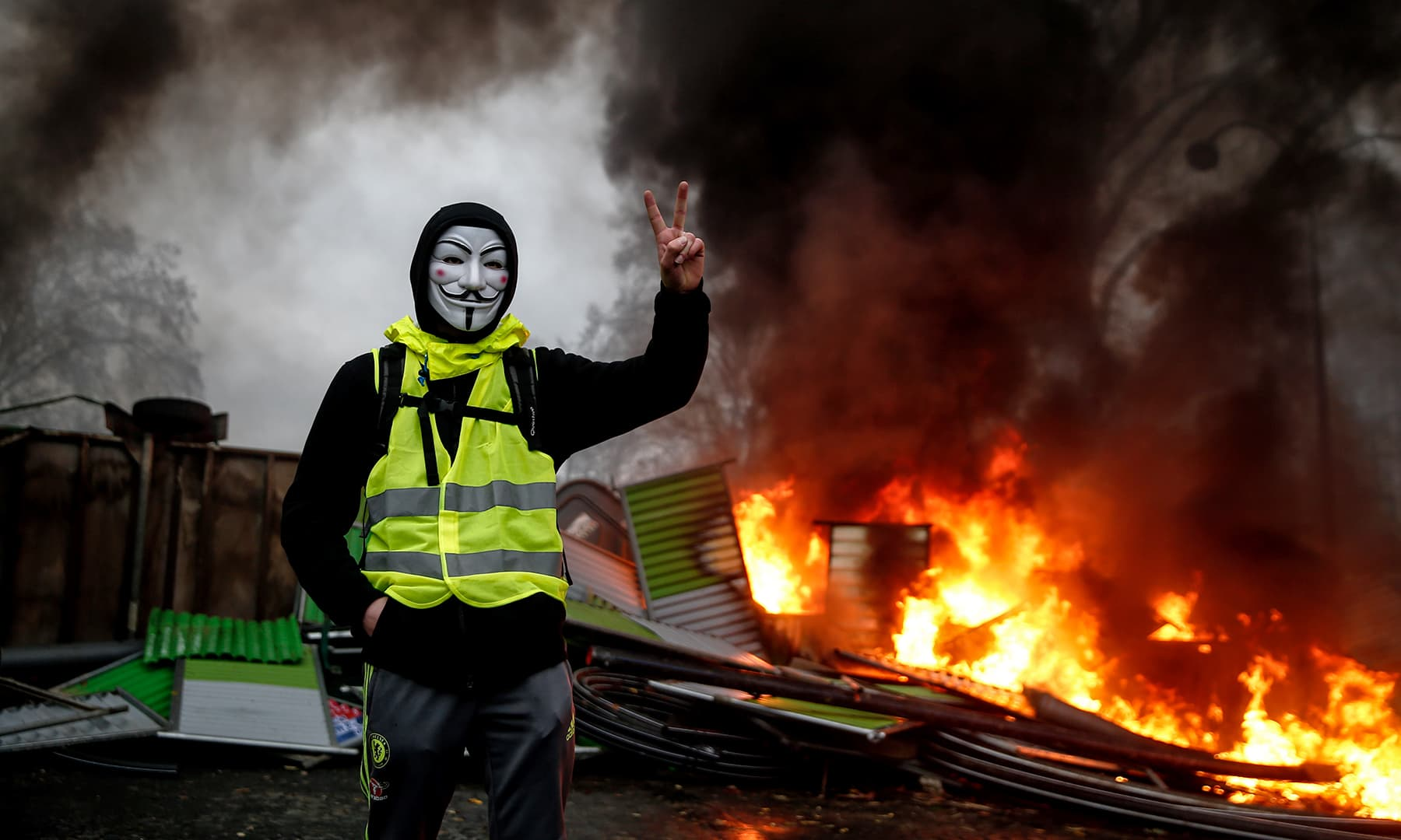 A protester wearing a Guy Fawkes mask makes the victory sign near a burning barricade. —AFP