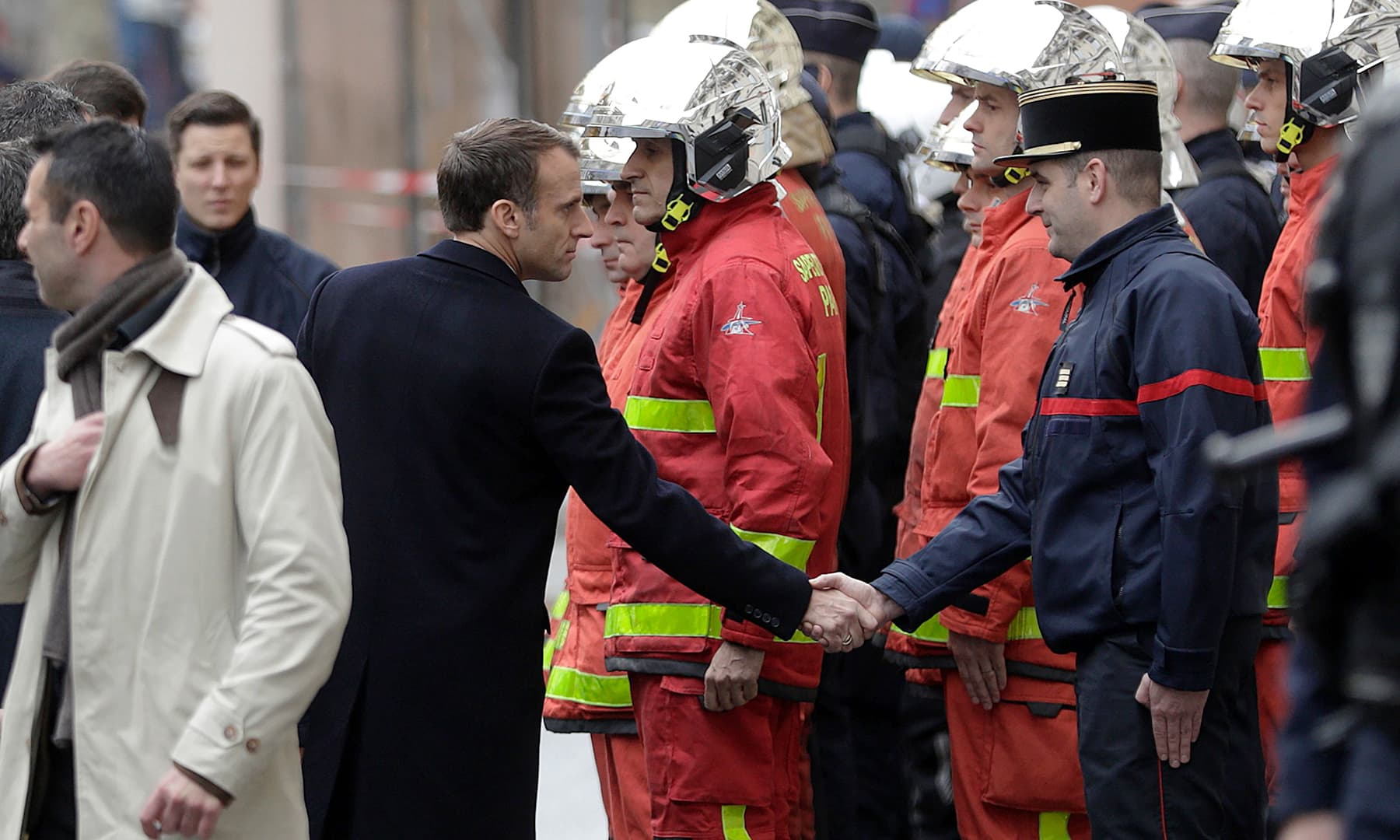 French President Emmanuel Macron shakes hands with a firefighter during a visit in the streets of Paris. —AFP