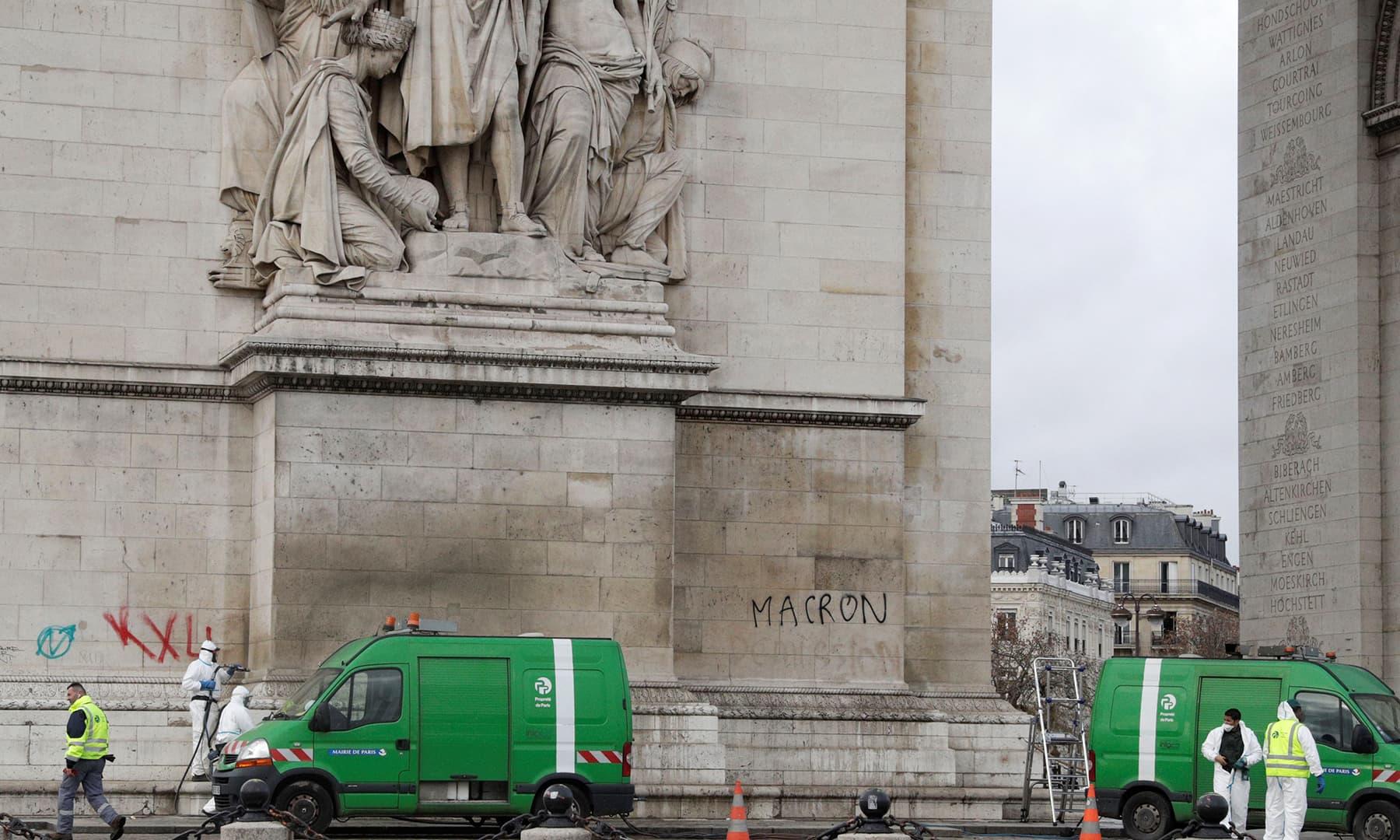 Workers scrub clean the graffiti littered Arc de Triomphe in Paris. —AFP