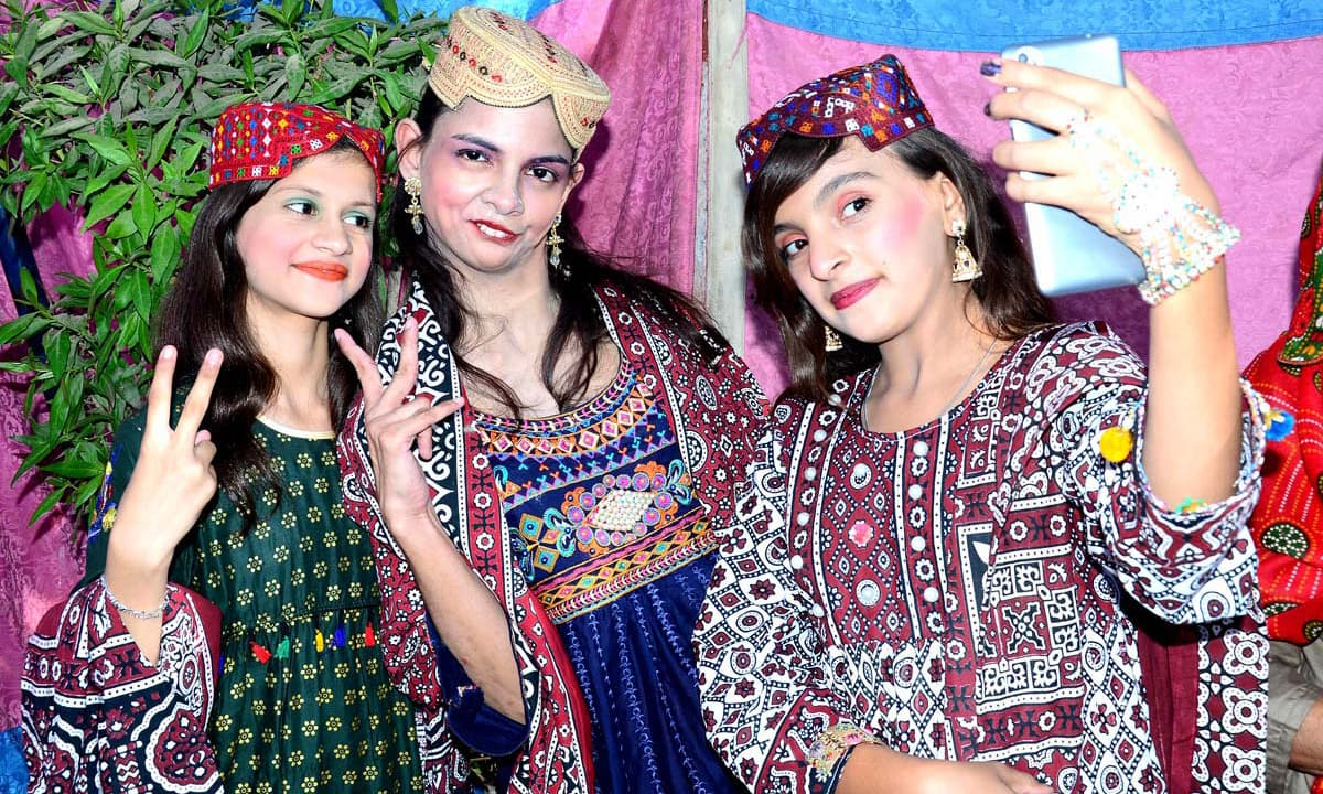 Girls wearing traditional dresses pose for selfies. —APP