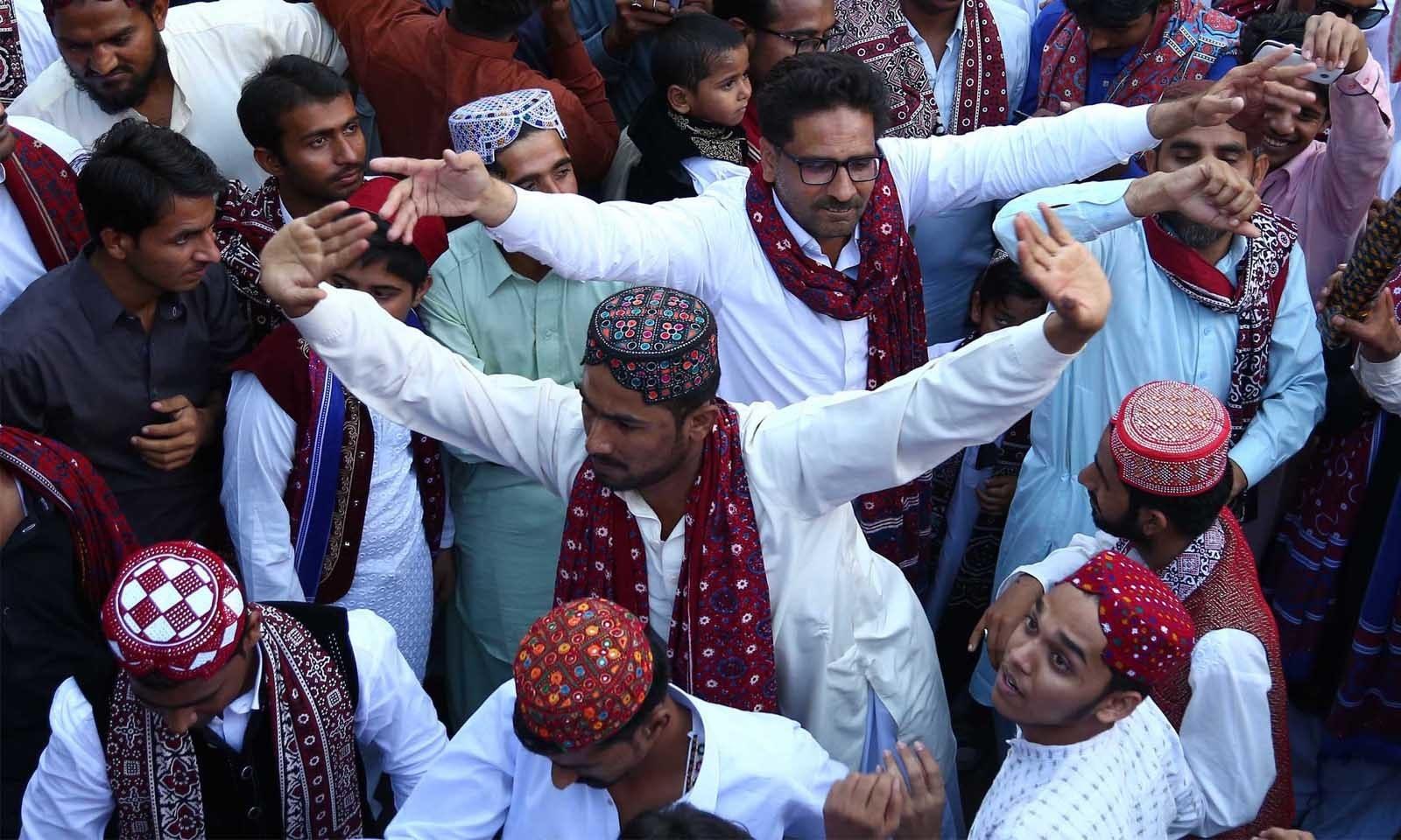 بزرگ ہوں یا نوجوان سب روایتی سندھی ملبوسات کے ساتھ سندھی لوک گیتوں کے مدھم سروں اور ڈھول کی تھاپ پر رقص کر رہے ہوتے ہیں—فوٹو: وقاص علی