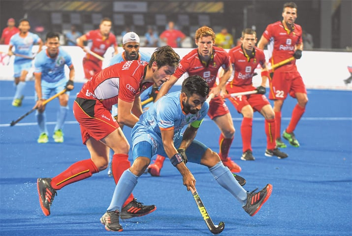 BHUBANESWAR: India's Manpreet Singh (C) tries to dribble past Belgium players during their pool stage World Cup match at the Kalinga Stadium on Sunday.—AFP