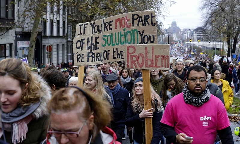 "People hold a sign reading ""If you're not part of the solution you're part of the problem"" during the ""Claim the Climate"" march to raise awareness for climate change, in Brussels. — AFP"